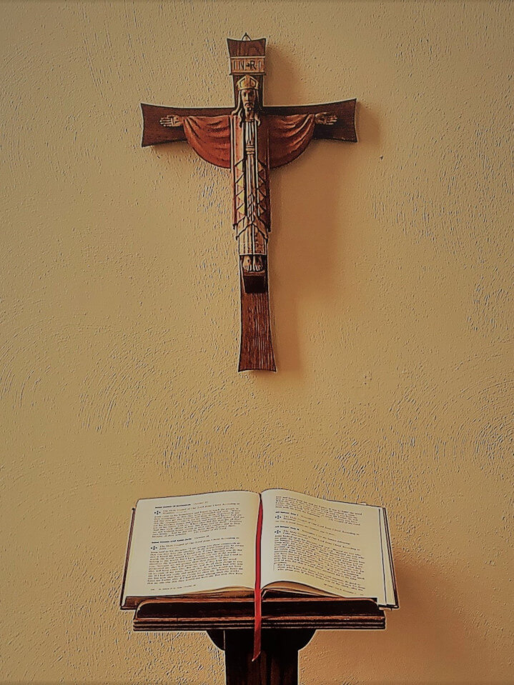 Open Bible with a cross hanging above it.