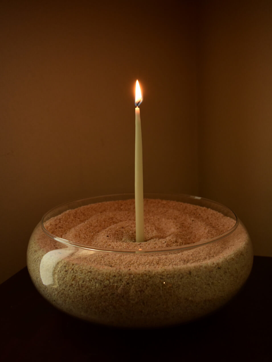 Glowing candle in a bowl of sand.