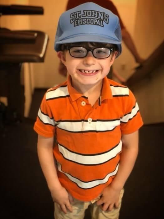 Child wearing a St. John's baseball hat.